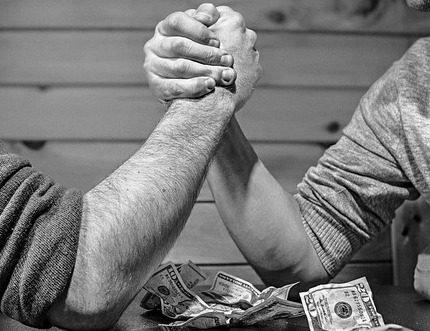 мужчины борятся на руках на столе с деньгами